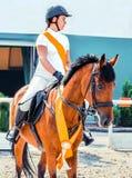 Het paard van de baaidressuur en de mooie meisjes Arabische verschijning in witte eenvormig bij tonen de springende concurrentie royalty-vrije stock foto's