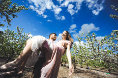 Het paarportret van een meisje en de kerel die een huwelijk zoeken kleden zich, een roze kleding die met een kroon van bloemen op Royalty-vrije Stock Fotografie