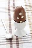 Het paasei van de chocolade in eierdopje en lepel Stock Foto's