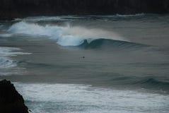 Het padling van Surfer tegen een golf Stock Foto