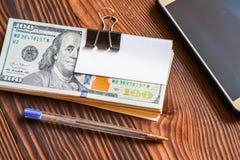 Het pak dollars telefoneert pen en document sticker voor uw tekst op houten achtergrond royalty-vrije stock afbeeldingen