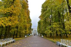 Het paleis aan het eind van de weg met dalingsgebladerte en gele bomen stock afbeelding