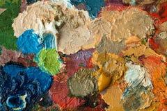 Het palet van kunstenaars met gemengde olieverf stock foto