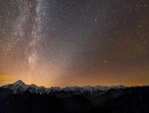 Het panorama van het de nachtlandschap van de winterbergen Melkweg heldere constellatie in donkere sterrige hemel, zachte gloed o stock afbeeldingen