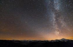 Het panorama van het de nachtlandschap van de winterbergen Melkweg heldere constellatie in donkere sterrige hemel, zachte gloed o royalty-vrije stock afbeeldingen