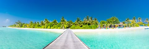 Het panorama van het het eilandstrand van de Maldiven Palmen en strandbar en lange houten pijlerweg Tropische vakantie en de zome royalty-vrije stock fotografie