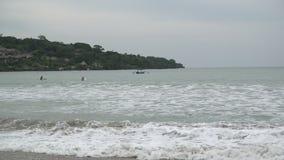 Het panorama van het strand van Bali Jimbaran Indonesië, Rode vlag een signaal van het verbod om wegens een grote golf, surfers t stock videobeelden