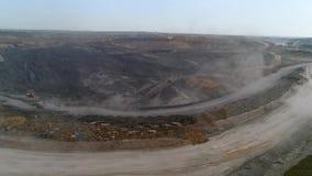 Het panoramasatellietbeeld schoot de mijnbouw van de open kuilmijn, kipwagens, die het mijnbouw ontdoende van werk uithakken Grot stock footage