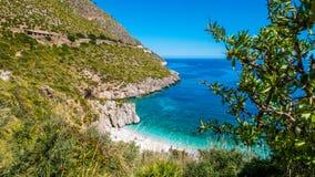 Het paradijsstrand: duidelijk turkoois zeewater, wit die kiezelstenenstrand, van achter luxuriant vegetatie wordt bevlekt Royalty-vrije Stock Afbeelding