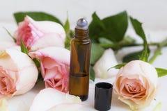Het parfum van de rozenolie in rolfles met rozenbloemen royalty-vrije stock afbeelding