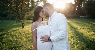 In het park komt een mens aan zijn zwangere haar vrouw, kussen en het strijken buik 4K stock video