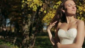 Het park van de bruidherfst in een witte kleding die bij camera possing stock footage