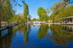 Het park van de stad met een brug en een vijver Stock Afbeelding