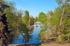 Het park van de stad met een brug en een vijver Royalty-vrije Stock Foto's