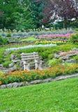 Het park van de zomer, bank in een tuin, bloemen, installaties Royalty-vrije Stock Fotografie