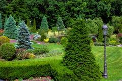 Het park wordt gemodelleerd met een groen gazon en bloembedden stock foto