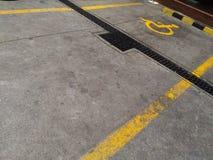 Het parkeerterrein voor maakt personen onbruikbaar merkte geel geschilderd teken op de vloer stock afbeeldingen