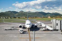 Het parkeren van het Airacraftvliegtuig bij luchthaven dichtbij groene bergen die worden geladen Stock Fotografie