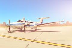 Het parkeren van het propellervliegtuig bij de luchthaven Zonnige dag Stock Afbeelding