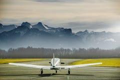 Het parkeren van het propellervliegtuig bij de luchthaven Klein vliegveld voor hooggebergte Zonsondergang over bergen Stock Fotografie