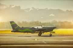 Het parkeren van het propellervliegtuig bij de luchthaven Klein vliegveld voor hooggebergte Zonsondergang over bergen Royalty-vrije Stock Foto
