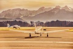Het parkeren van het propellervliegtuig bij de luchthaven Klein vliegveld voor hooggebergte Zonsondergang over bergen Stock Afbeelding