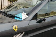 Het parkerenkaartje voor een sanctie of een boete plakte op luxueus die Ferrari auto` s voorruit, in de Koninklijke Stad wordt ge royalty-vrije stock afbeeldingen