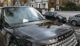 Het parkerenkaartje voor een sanctie of een boete plakte op Range Rover auto` s voorruit, in de Koninklijke Stad van Kensington w royalty-vrije stock fotografie