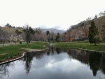 Het Parkmeningen van het geheugenbosje van Watervallen en stromen in een klein die vijver of een meer leiden door wegen wordt omr royalty-vrije stock afbeeldingen