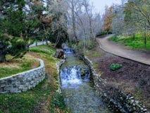Het Parkmeningen van het geheugenbosje van Watervallen en stromen in een klein die vijver of een meer leiden door wegen wordt omr stock afbeelding