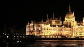 Het Parlement van Boedapest bij nacht terwijl het varen op een boot op de rivier Donau Timelapse stock videobeelden
