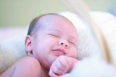 Het pasgeboren baby slaap en grijnzen Royalty-vrije Stock Foto