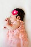 Het pasgeboren babymeisje slaapt, het kleden zich roze doeken, wat als rok, met hoofddeksel kijkt stock fotografie