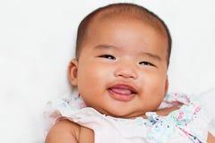 Het pasgeboren meisje die van de zuigelingsbaby op wit bed glimlachen stock foto