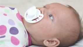 Het pasgeboren meisje liggen op het blad en zuigt fopspeen stock videobeelden