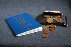 Het paspoort van de Oekraïne met Euro binnen Rekeningen Op een grijze backgraund stock foto's