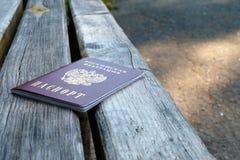 Het paspoort van de Russische Federatie ligt buiten op een houten bank stock afbeelding