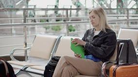 Het passagiersmeisje neemt tablet van zak, zittend in wachtkamer van luchthaven stock videobeelden
