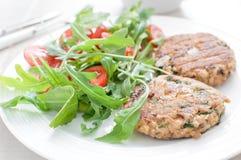 Het pasteitje van grondvissen met de salade van de arugulatomaat Royalty-vrije Stock Afbeeldingen