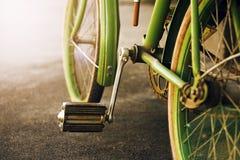 Het pedaal en de wielen van een oude uitstekende groene Fiets stock fotografie