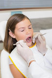 Het pediatrische tandarts onderzoeken kleine meisjestanden als tandartsenvoorzitter Stock Foto
