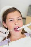 Het pediatrische tandarts onderzoeken kleine meisjestanden als tandartsenvoorzitter Royalty-vrije Stock Foto