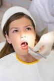 Het pediatrische tandarts onderzoeken patiëntentanden als tandartsenvoorzitter Stock Foto's