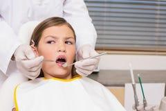 Het pediatrische tandarts onderzoeken patiëntentanden als tandartsenvoorzitter Stock Afbeeldingen