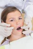 Het pediatrische tandarts onderzoeken patiëntentanden als tandartsenvoorzitter Stock Fotografie