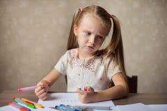 Het peinzende kind trekt met kleurpotloden Stock Foto