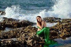 Het peinzende meisje in een groen meerminkostuum zit op de rotsen op de kust op de achtergrond van waterplonsen en kijkt aan sid royalty-vrije stock foto