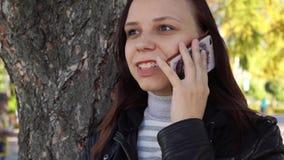 Het peinzende meisje met smartphone dient binnen stadspark in de vrouw bekijkt het scherm van mobiele telefoon tegen achtergrond  stock video