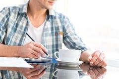 Het peinzende mens trekken en het drinken koffie in bureau Royalty-vrije Stock Afbeeldingen