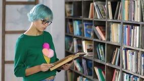 Het peinzende vrouwelijke boek van de studentenlezing in bibliotheek stock videobeelden